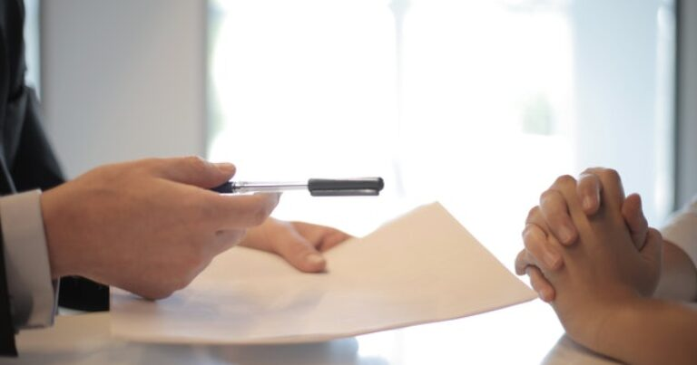 person handing a pen to sign contract