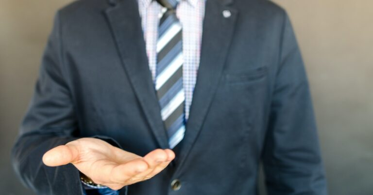 man in suit holding out his hand